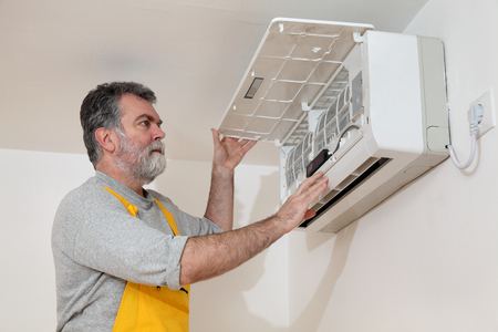 man in air: Electrician examine or install air condition device in a room