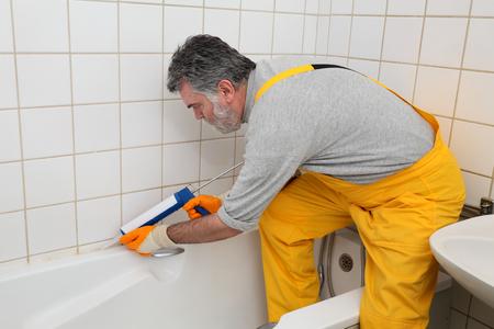 Plumber caulking bath tube with silicone glue using cartridge