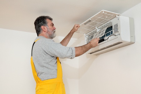 conditioner: Electrician cleaning filter of air condition device in a room