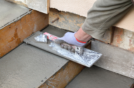 concrete form: Staircase making, worker finishing concrete with trowel, home renovation