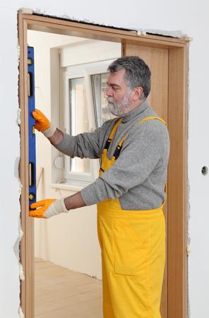 mesure: Worker install door, using level tool for mesure