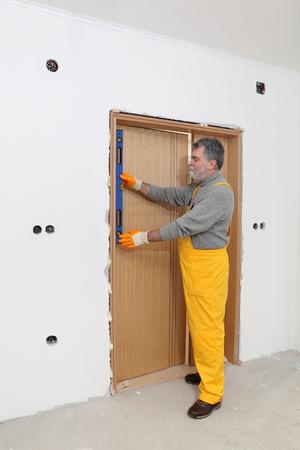 leveler: Worker install door, using level tool for mesure