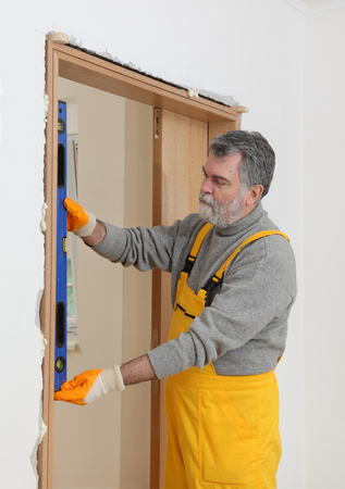 leveler: Worker install door, using level tool for measure verticality Stock Photo