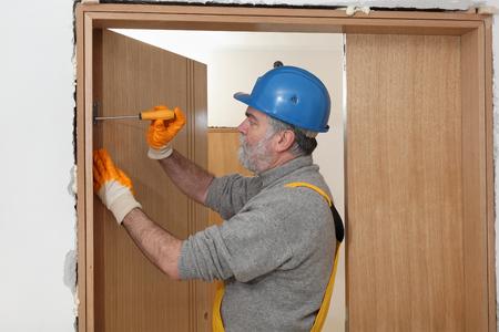 Worker fix door hinge with screwdriver, wearing gloves and helmet Standard-Bild