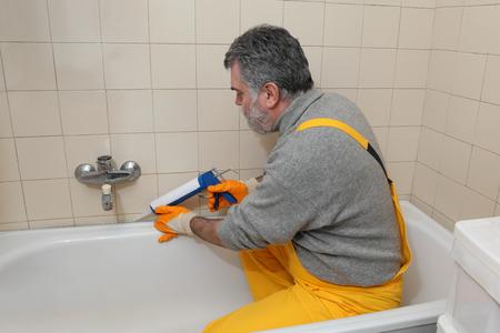 caulking: Plumber caulking bath tube with silicone glue using cartridge