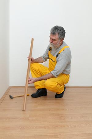 batten: Worker hold batten for laminate floor and hammer,  floating wood tile Stock Photo