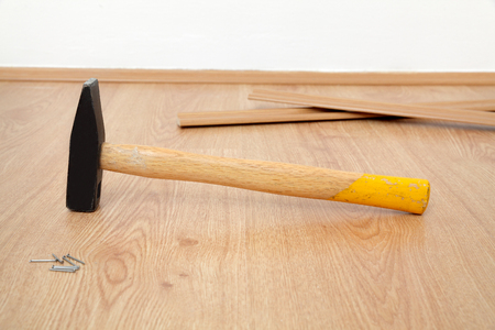 parquet floor: Closeup of hammer, nails and batten for laminate floor, floating wood tile
