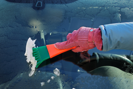 scraping: Winter scene, human hand in glove scraping ice from windshield of car