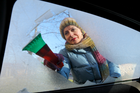 Winter scene, adult woman scraping ice from windshield of car