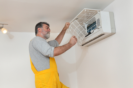 setup man: Electrician cleaning filter of air condition device in a room