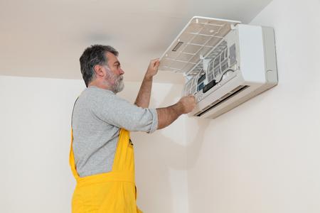 Elektricien reinigen filter van airconditioning apparaat in een ruimte