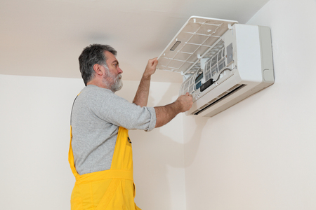 aire acondicionado: Filtro de limpieza del electricista de dispositivo de aire acondicionado en una habitación Foto de archivo