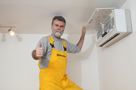 Electrician examine or install air condition device, gesturing with thumb up