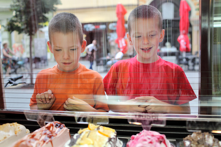 icecream: Two young Caucasian boy looking ice cream in pastry shop, real people