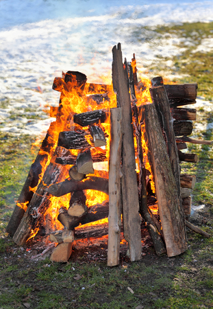burning time: Big campfire, heap of wooden logs burning outdoor in winter time