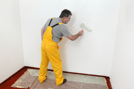 painting and decorating: Worker painting wall to white with paint roller
