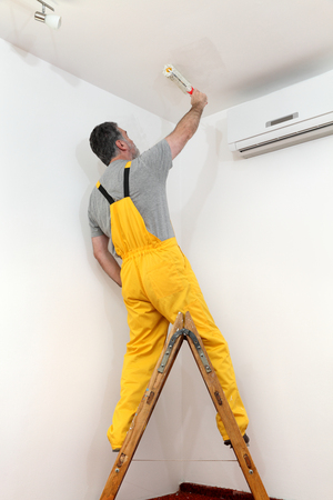 redecoration: Worker painting ceiling to white color with paint roller