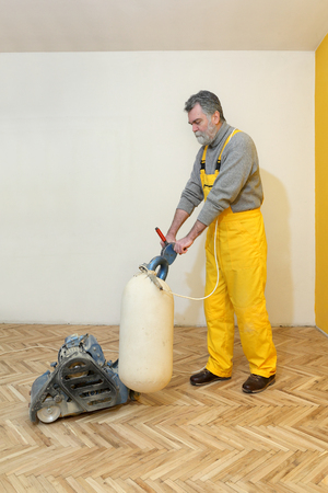 craftman: Worker polishing old parquet floor with grinding machine Stock Photo
