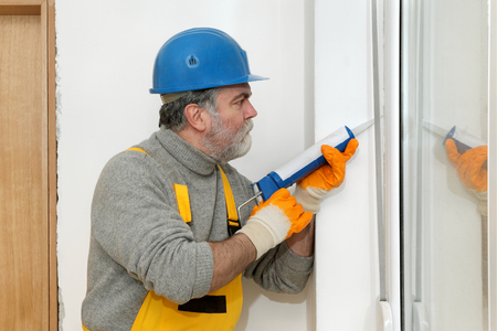 window seal: Construction worker caulking door or window with silicone glue using cartridge