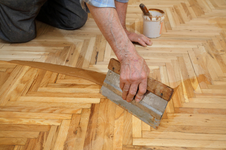 treated board: Varnishing of oak parquet floor, senior workers hand and tool, 77 year old senior worker