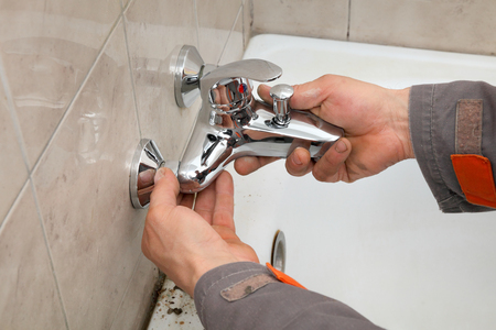 Plumber hands fixing water  tap in a bathroom