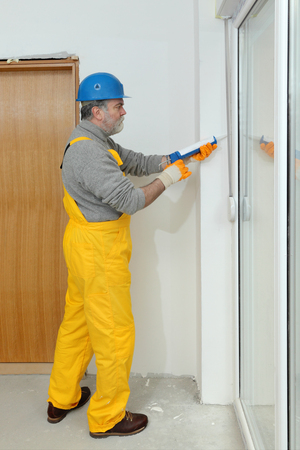 caulking: Construction worker caulking door or window with silicone glue using cartridge