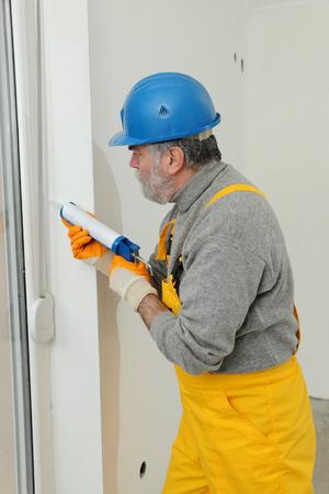 caulking: Construction worker caulking door or window with silicone glue using cartridge