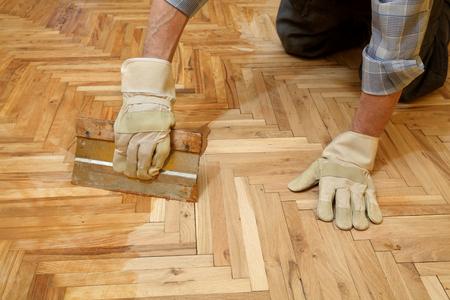 オーク材の寄木細工の床、労働者の手およびツールのニスを塗る 写真素材 - 37699249