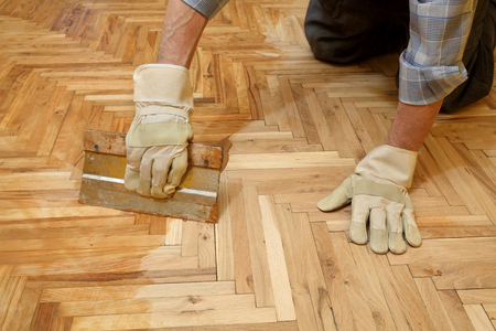 Varnishing of oak parquet floor, workers hand and tool Stock fotó - 37699249