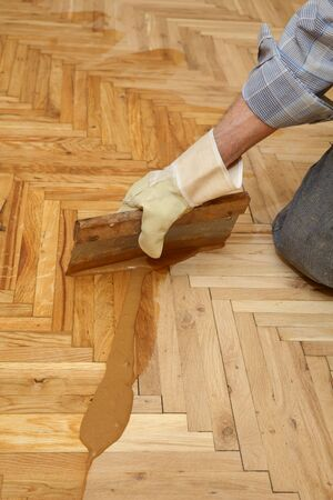 parquet floor layer: Varnishing of oak parquet floor, workers hand and tool Stock Photo