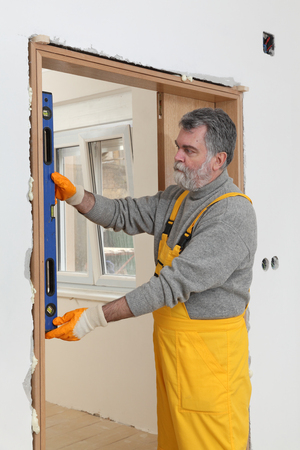 leveler: Home renovation, worker install door, using level tool for measure
