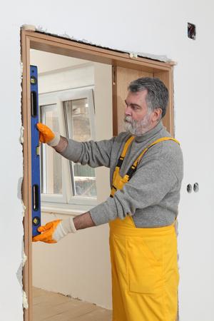 PUERTA: Renovaci�n del hogar, trabajador instalar puerta, usando la herramienta nivel de medida Foto de archivo