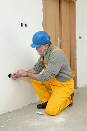 socket: Electrician installing electrical plug at wall and using voltage testing screwdriver