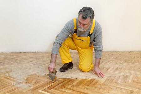 parquet floor layer: Varnishing of oak parquet floor, mature adult worker using tool