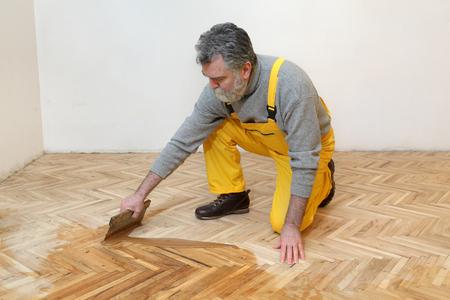 materiales de construccion: Barnizado de suelos de parquet de roble, trabajador adulto maduro con el �til Foto de archivo