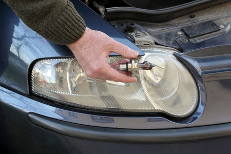 Human hand holding broken H4 car light bulb, mechanic servicing light Standard-Bild