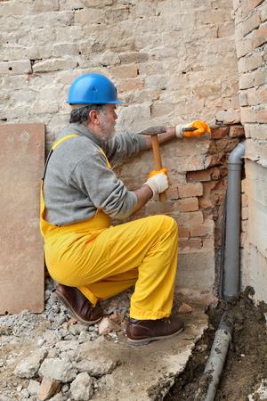 Huis renovatie, loodgieter installeren riolering pijp op de bouwplaats met behulp van hamer en beitel