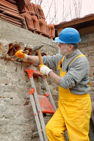 demolishing: Construction worker demolishing old brick wall with chisel tool and hammer
