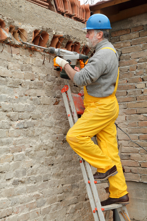 demolishing: Construction worker demolishing brick wall with electric plugger, chisel hammer tool Stock Photo