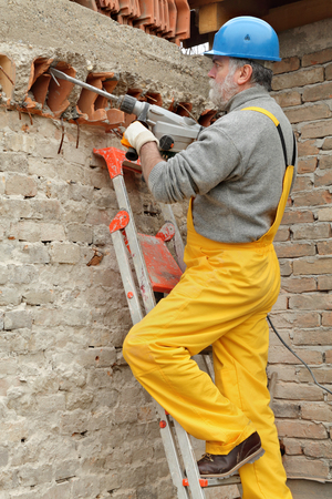 demolishing: Construction worker demolishing brick wall with electric plugger, chisel hammer tool Stock Photo