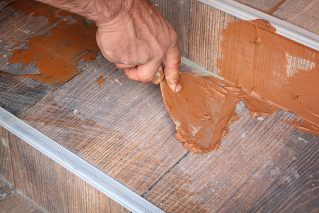 tile adhesive: Joint sealing tiles, worker hand and trowel tool