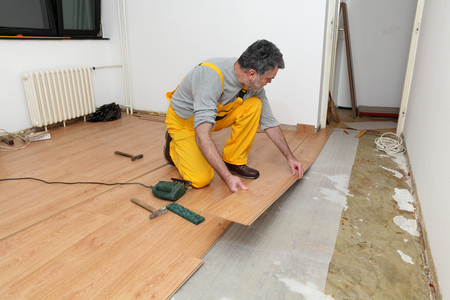 Adult male worker installing laminate floor,  floating wood tile photo