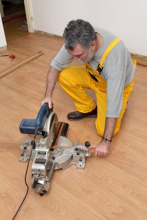 batten: Worker cut wooden batten for laminate floor,  floating wood tile