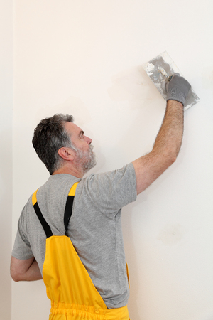 Worker spreading plaster to wall with trowel, repairing works