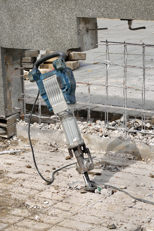 stone work: Electric plugger hammer with at construction site