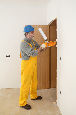 polyurethane: Worker install door, using polyurethane foam to fix it at wall