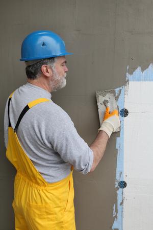 Arbeider verspreiden mortel dan piepschuim isolatie en mesh met troffel Stockfoto