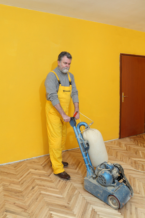 Worker polishing, sanding old parquet floor with grinding machine photo