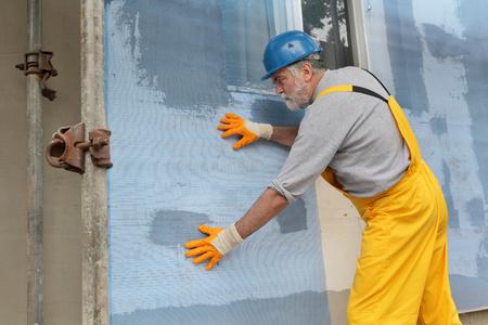 styrofoam: Worker placing mesh over styrofoam insulation and mortar
