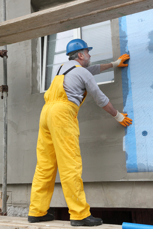 by placing: Worker placing mesh over styrofoam insulation and mortar